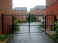 A steel gate with no curves and hoops along the top.