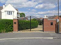 A steel gate with a double middle rail and serpentine curved double top rail