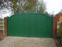 A pair of 'Derby' gates painted green. The 'Derby' design has a single convex curve flattening out towards the centre giving a slightly more imposing look than the Buxton design.