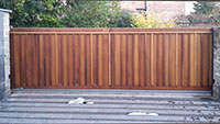 A modern looking wooden flat topped sliding gate
